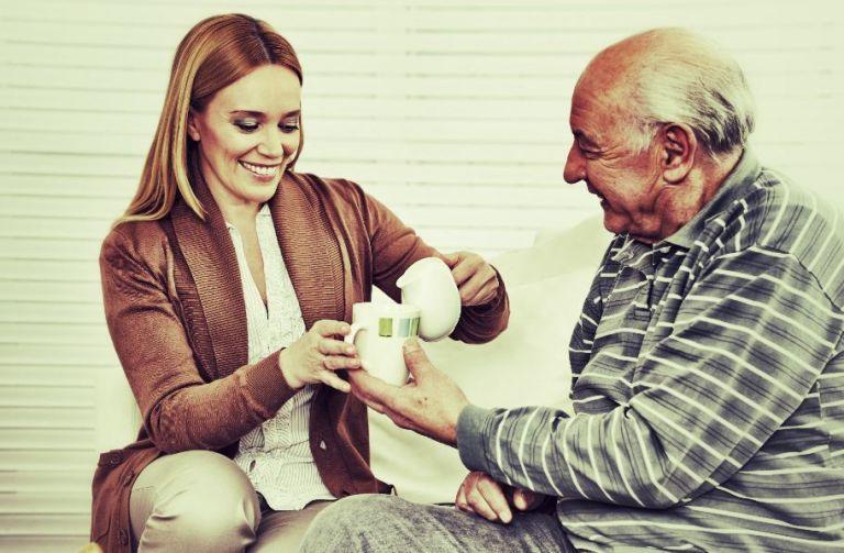 femme sert un verre de lait à un seniorpour calcium
