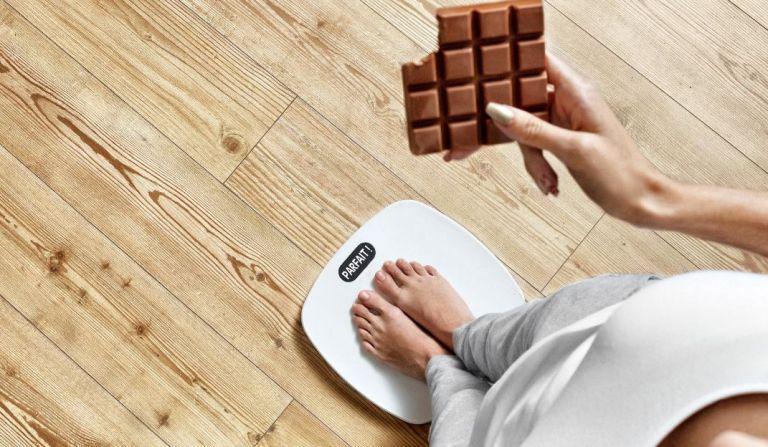 une femme se pese pour connaitre son poids ideal