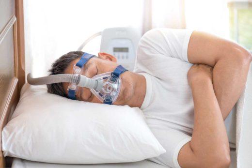 Homme dormant au lit portant un masque, contre apnée du sommeil