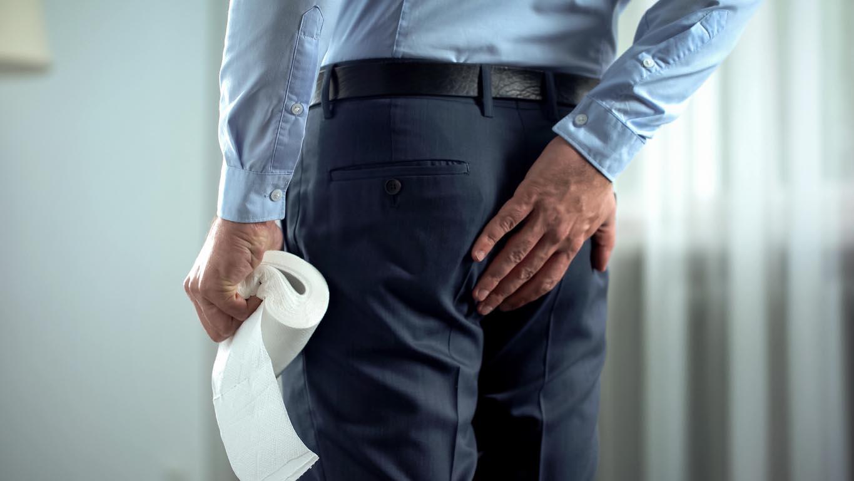 Employé de bureau avec du papier de toilette dans la main souffre de douleurs d'hémorroïdes