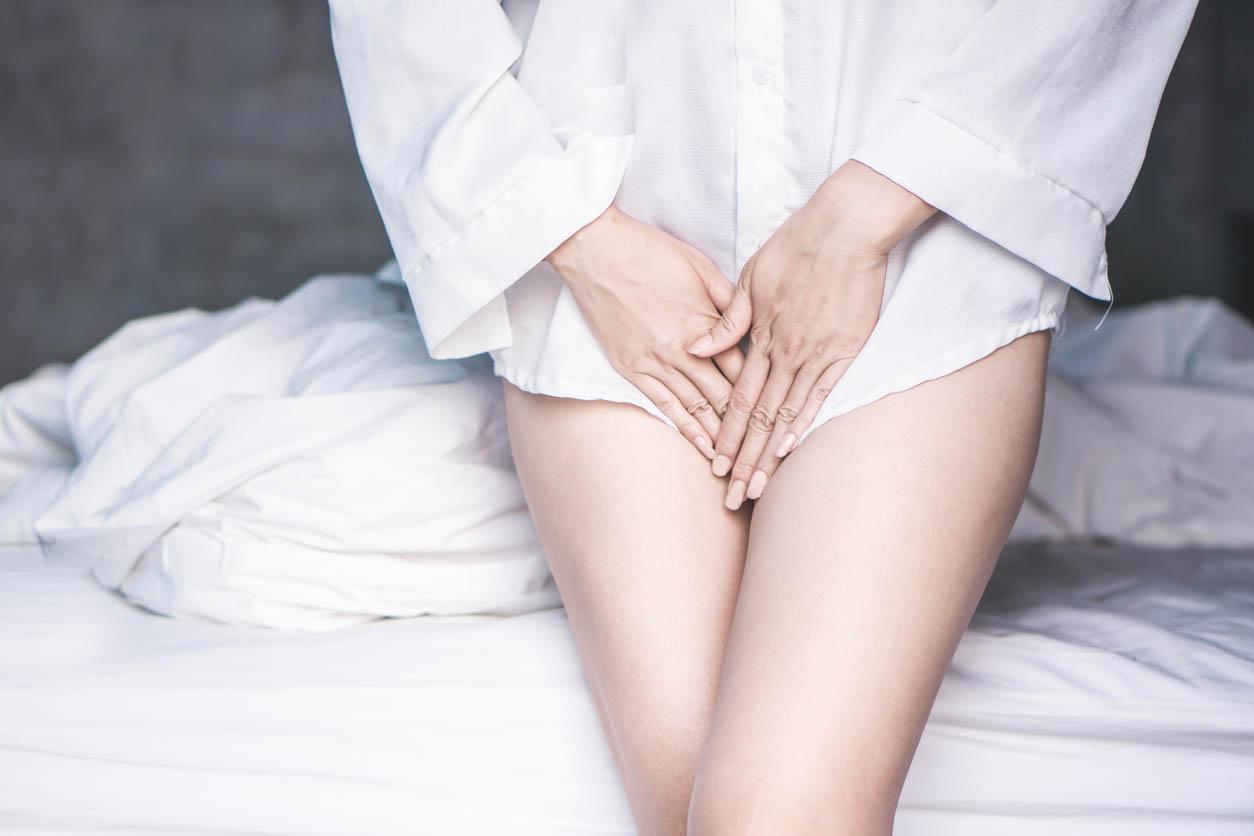 Main de femme retenant son entrejambe souffrant de douleur liés à la cystite