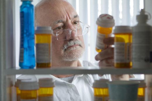 Senior homme regardant les médicaments sur ordonnance médicale