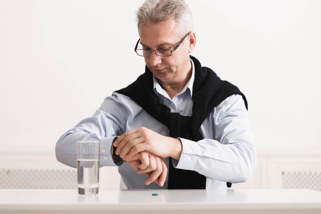 senior qui regarde sa montre pour prendre son medicament