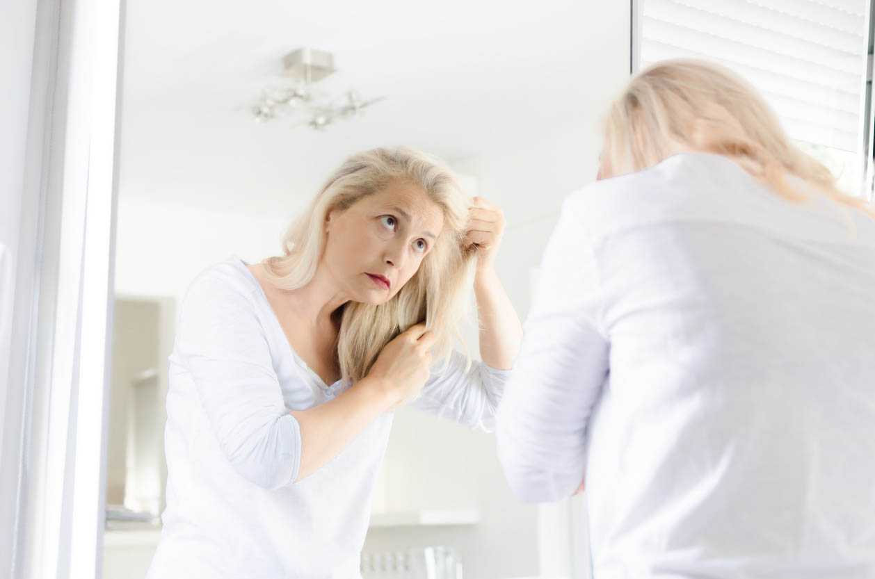 Woman Looking Hair In A Mirror