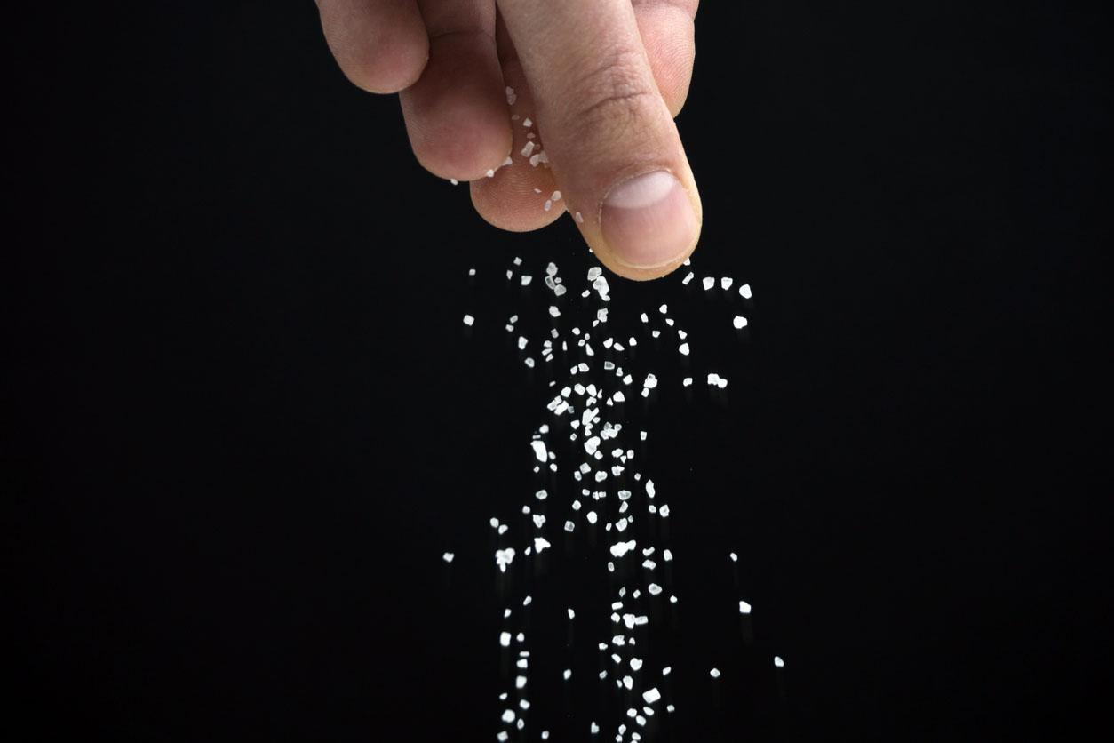 Hands Spreading Salt On Black Background
