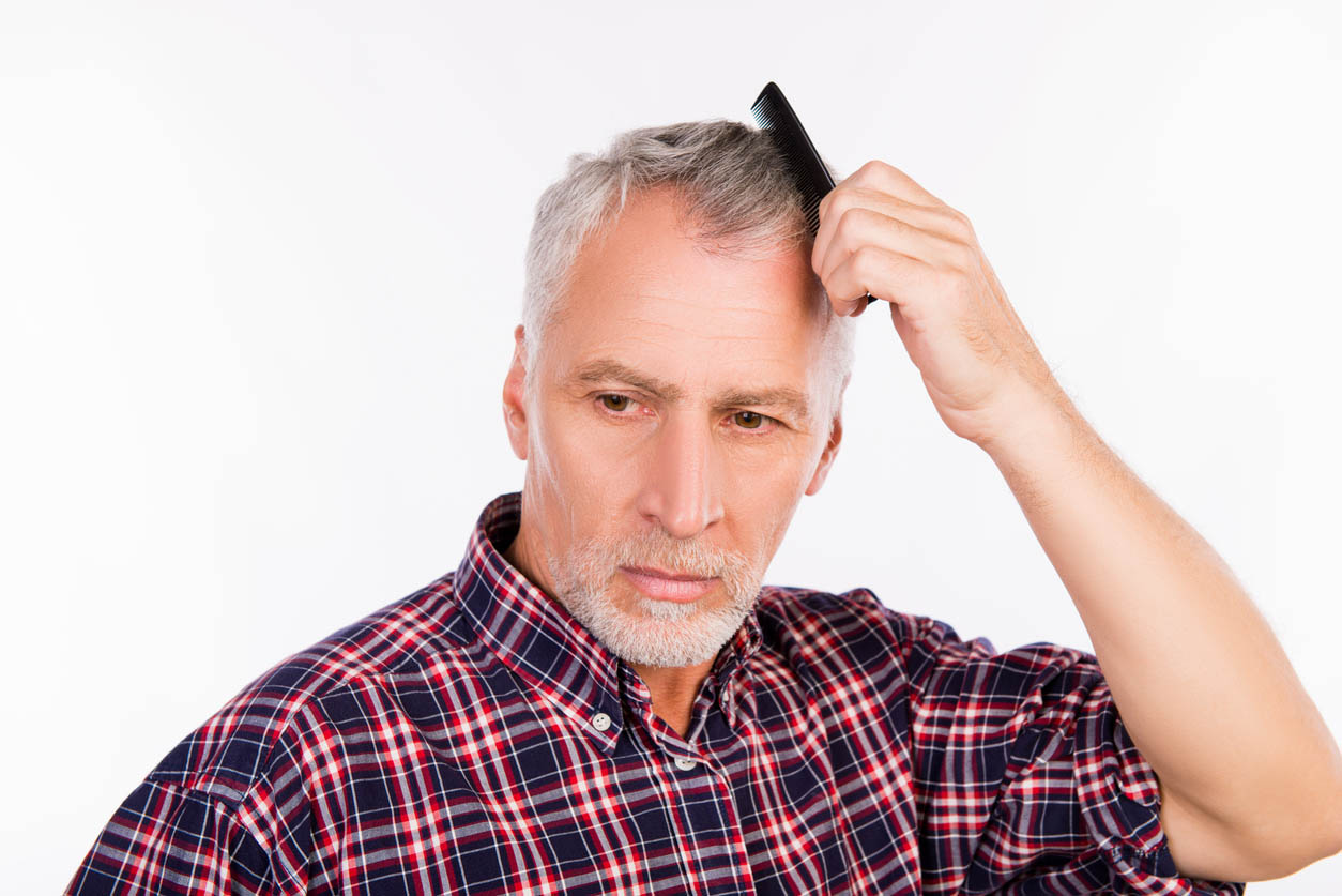 Homme âgé gris bouleversé peignant ses cheveux