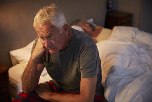 senior triste assis sur un lit