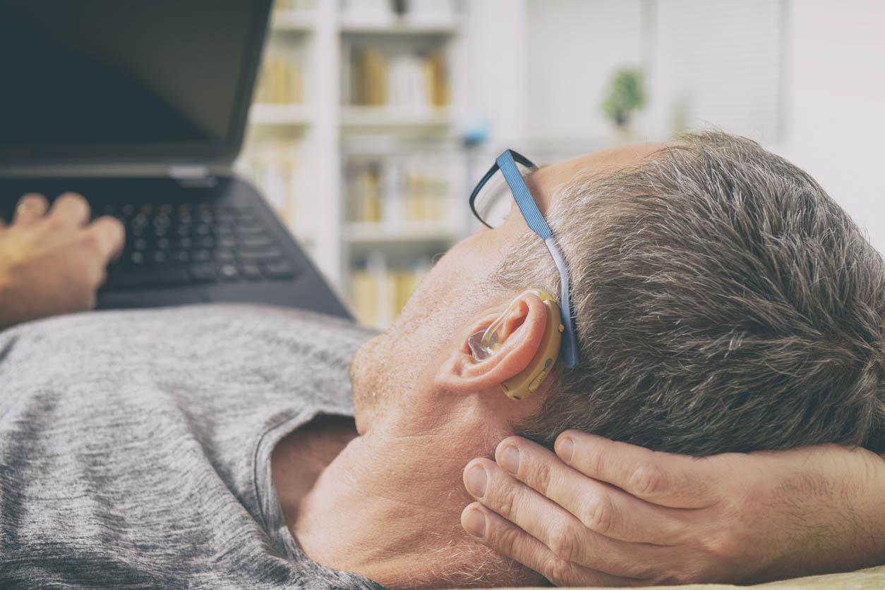 homme équipé d'un appareil auditif devant un ecran ordinateur