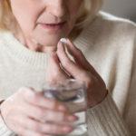 femme mure senior tenant le verre d'eau et un cachet