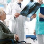 Médecin contrôlant une image radiographique de la patiente âgée lors d'une visite à l'hôpital, pour l'ostéoporose