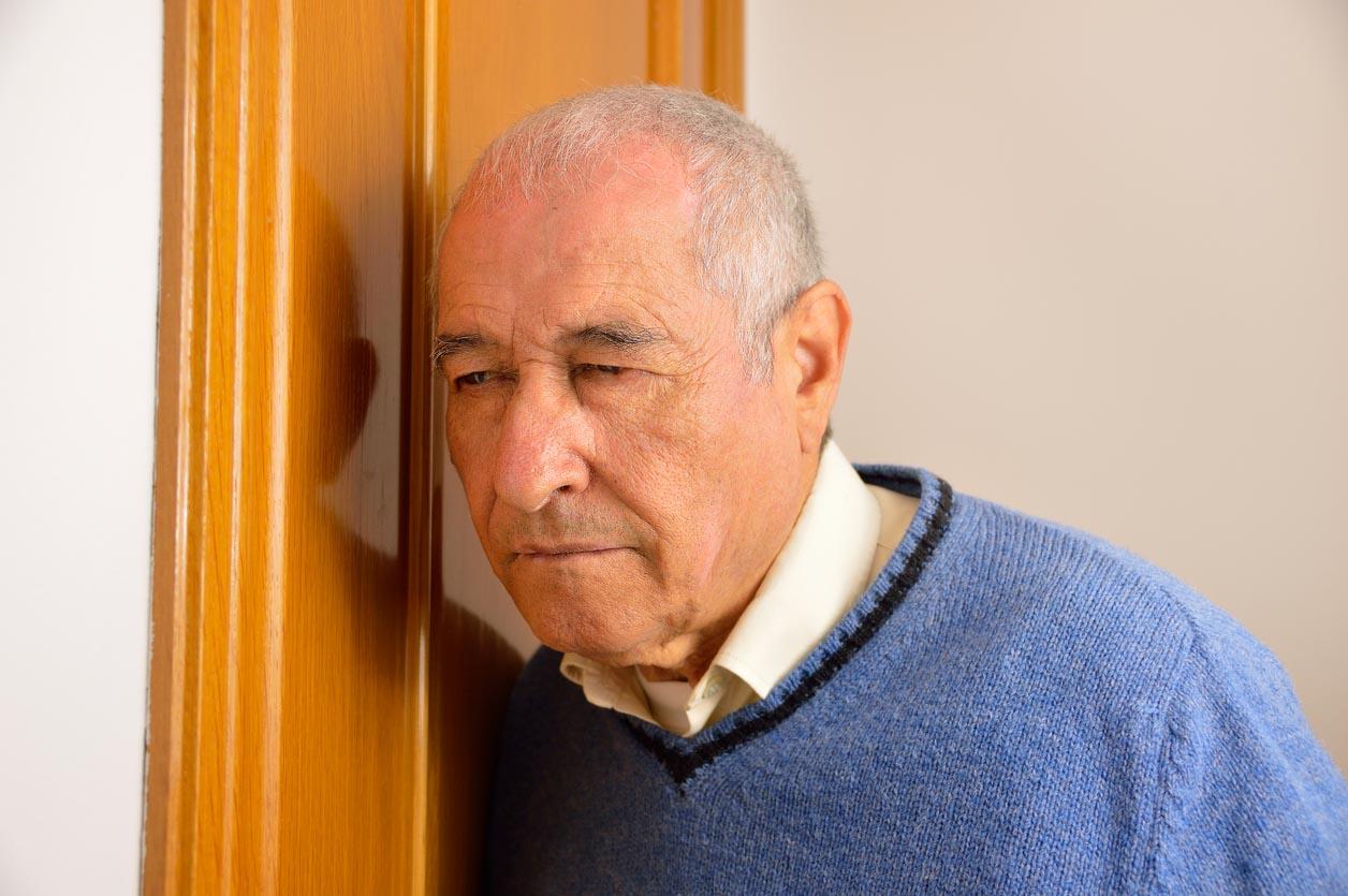 Senior homme écoute derrière la porte de son voisin