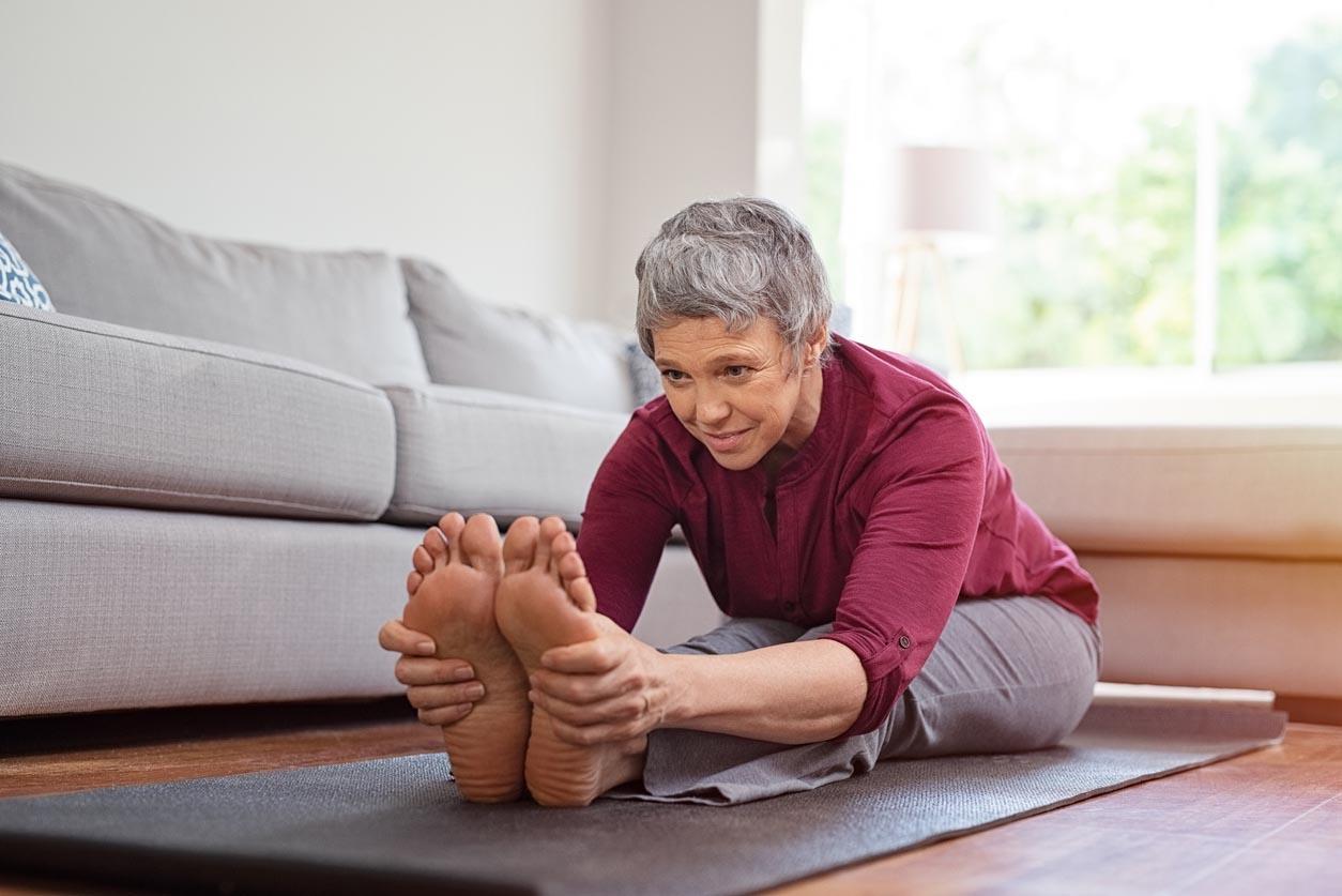 Femme mature, faire des exercices d'yoga à la maison
