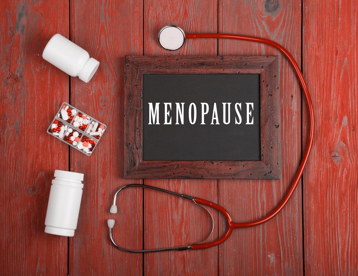 Tableau noir avec texte « Ménopause », stéthoscope, pilules sur fond en bois bleu