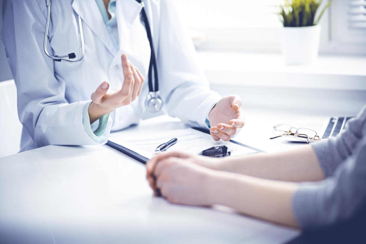 Doctor And Female Patient Sitting At The Desk And Talking In Clinic Near Window. Medicine And Health Care Concept. Green Is Main Color
