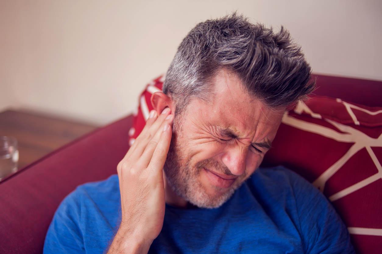 homme ressent une forte douleur auditive