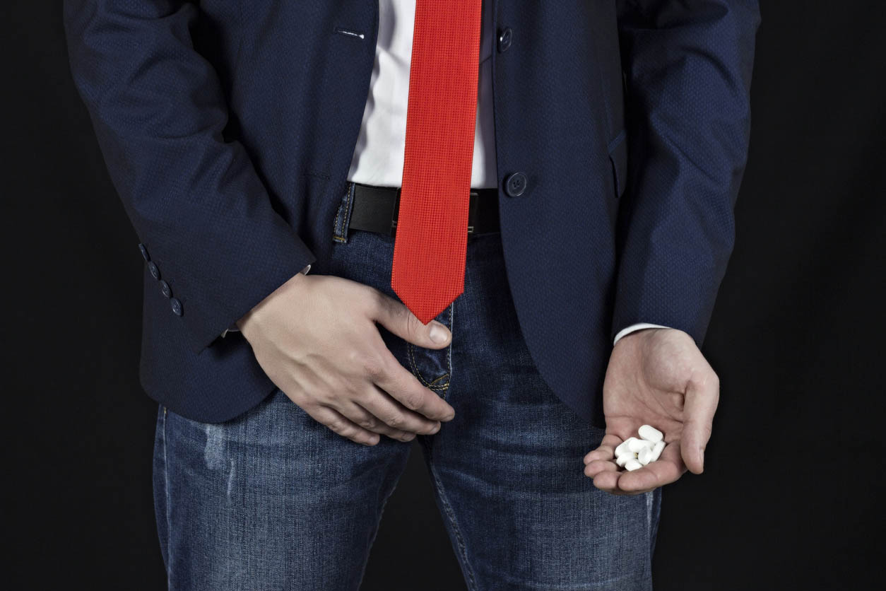 Businessman Holds A Groin, A Handful Of Pills In Her Hand