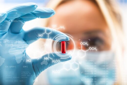 Young Attractive Female Scientist Holding A Red Transparent Pill