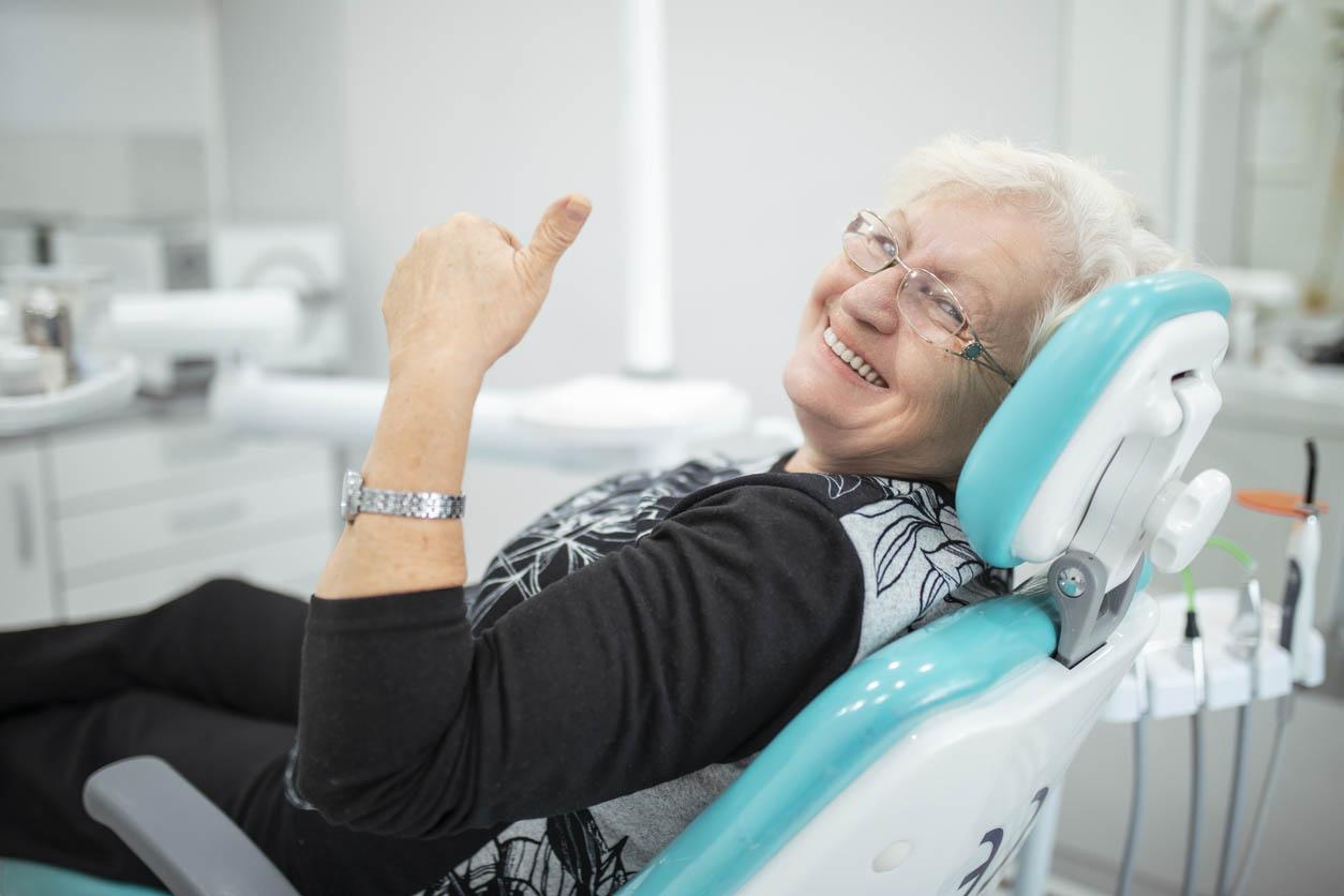 femme senior assise dans un cabinet dentaire