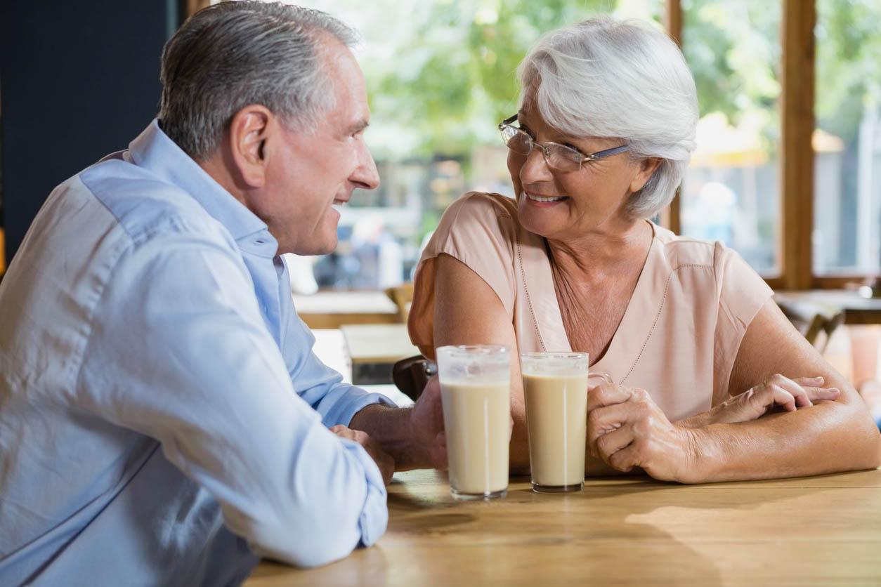 Happy Senior Couple Interacting While Having Coffee