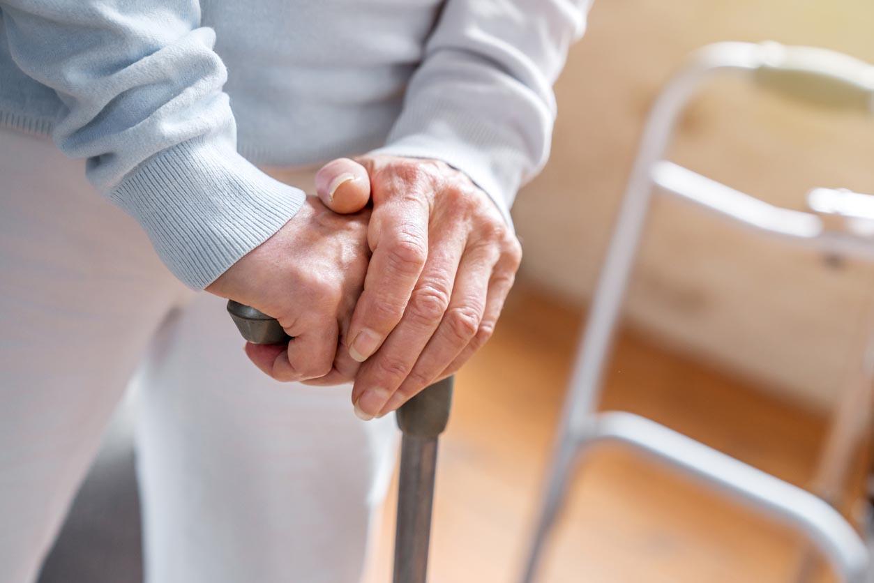 mains de femme aînée tenant une canne