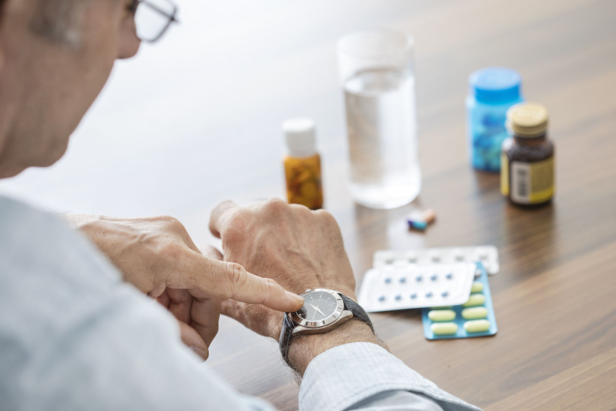 homme agé qui regarde sa montre pour prendre ses médicaments