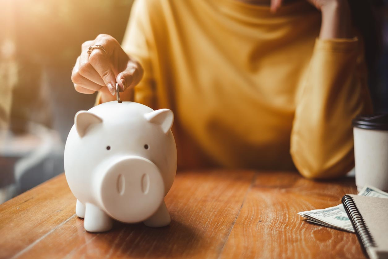 Woman Hand Putting Money Coin Into Piggy For Saving Money Wealth And Financial Concept.