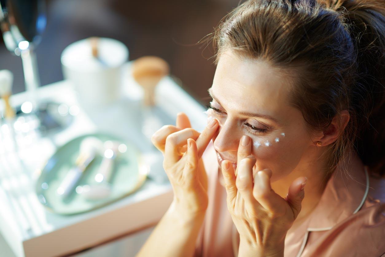 Female At Modern Home In Sunny Winter Day Applying Eye Cream