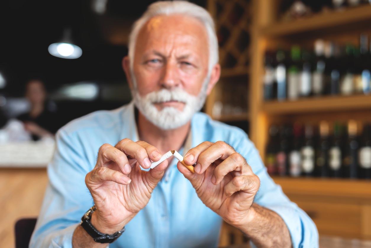 Homme aîné cassant la cigarette car elle est préjudiciable à la santé