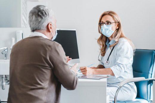 Le docteur de femme portent le masque de visage de protection parlant avec le patient dans le bureau de clinique