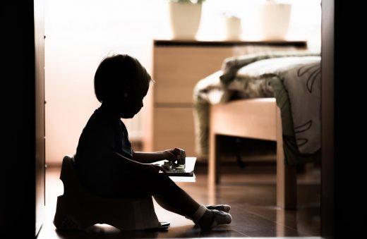 Cute Little Boy Sitting On A Potty.