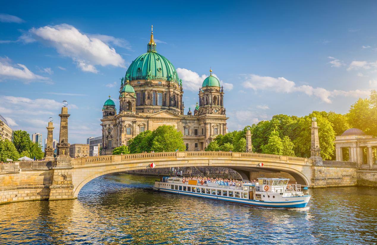 Cathédrale de Berlin avec le bateau sur la rivière Spree au coucher du soleil