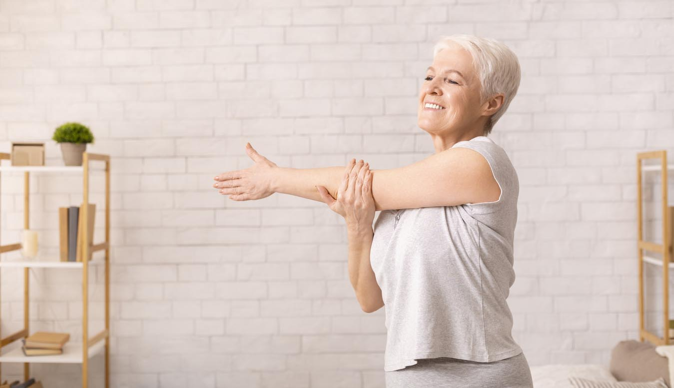 Positive Senior Lady Warming Up Her Hands At Home