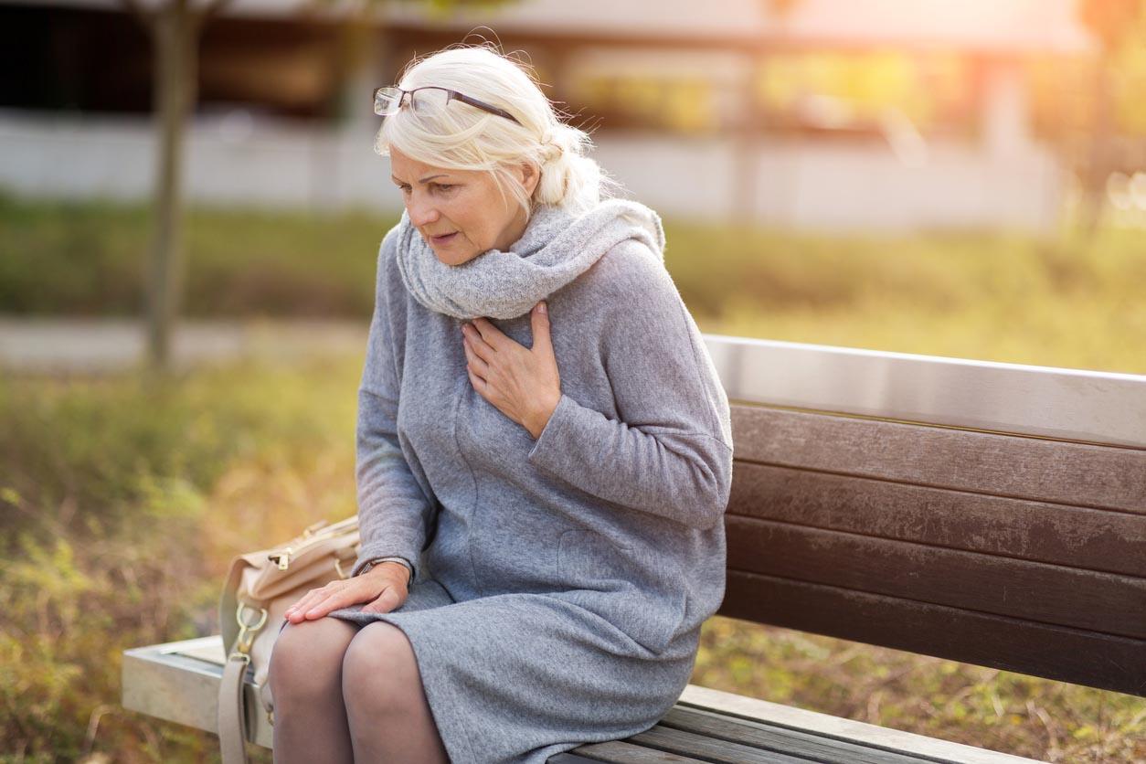 femme senior souffrant de douleurs à la poitrine tout en étant assis sur le banc