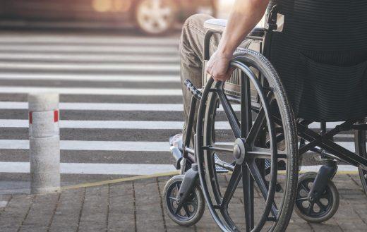 senior en fauteuil roulant en traversant la route