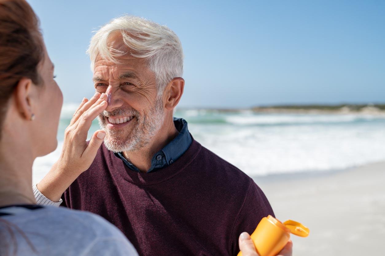 Femme appliquant la protection solaire sur le nez d'un homme mure
