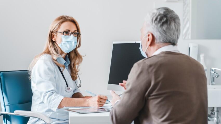 femme medecin qui porte un masque devant son patient pour faire un check up