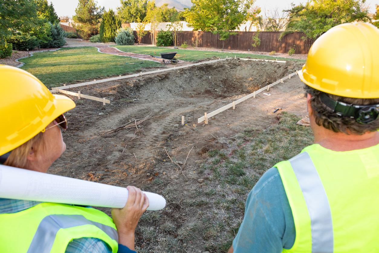 ravailleurs masculins et féminins donnant sur le chantier de Construction de piscine